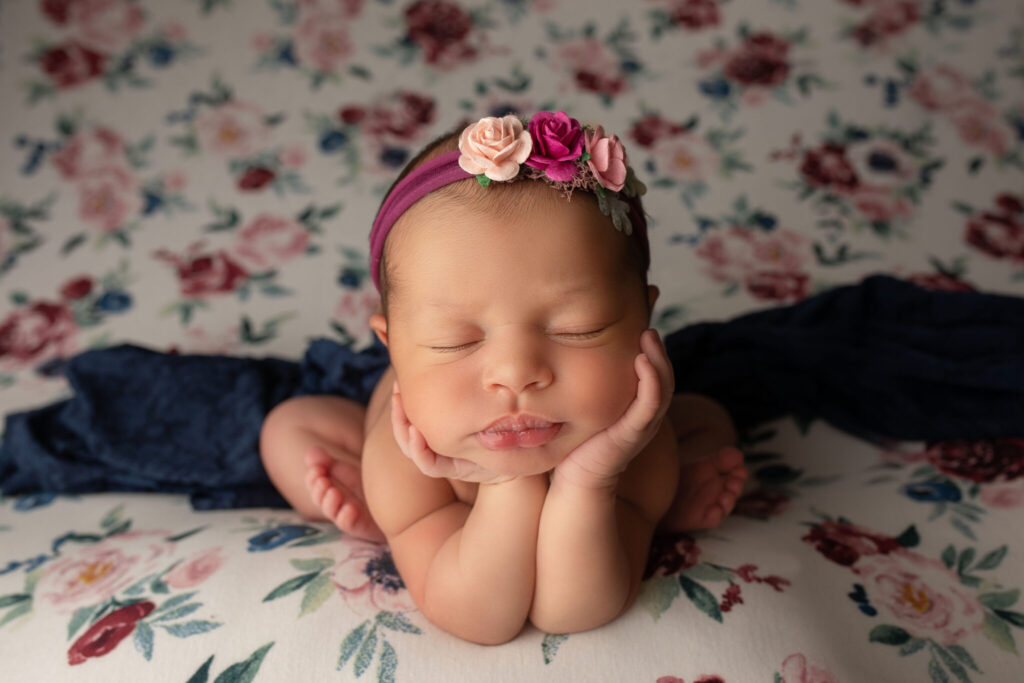 Baby girl sleeping with her head on her hands while lying on a floral drop.