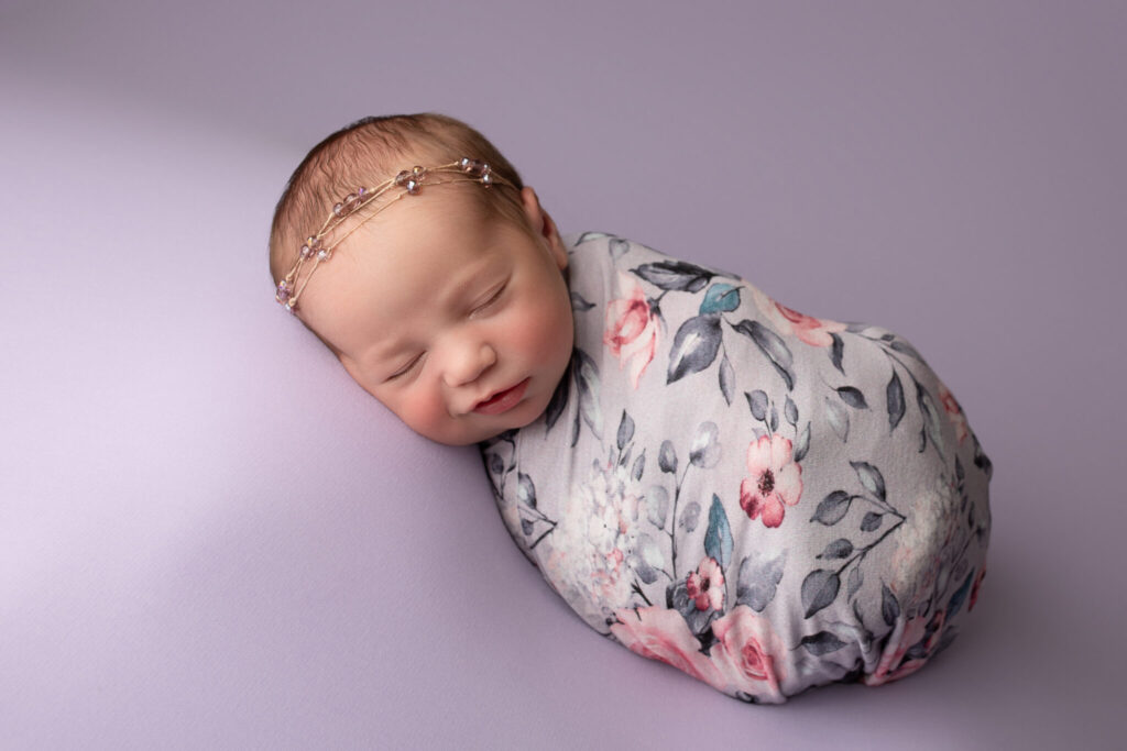 Smiling sleepy baby girl wrapped in a purple floral wrap.