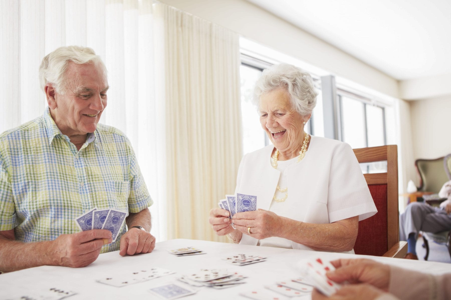 Senior adults playing cards