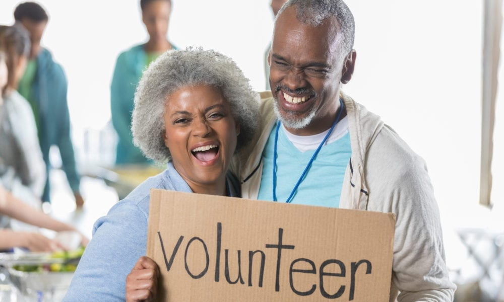 """happy couple holding a """"volunteer"""" sign at food bank"""