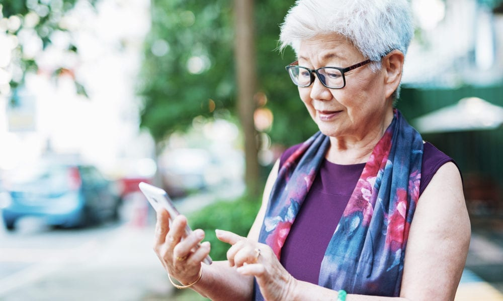 senior asian woman looking at smartphone while on a walk