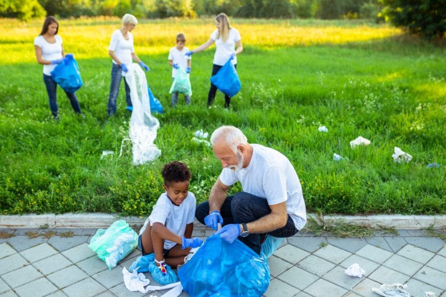Volunteers with garbage bags cleaning up garbage outdoors - ecology concept.