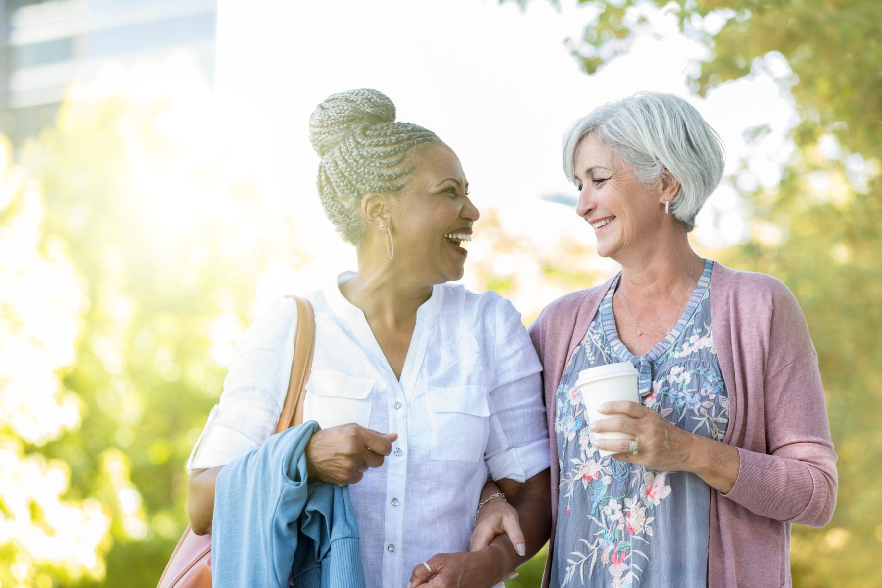 Two senior women walk arm in arm in a city park. One carries coffee as they look at each other and laugh.