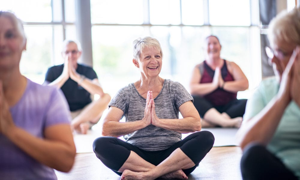 A group of seniors are sitting crosslegged and meditating in a fitness center.
