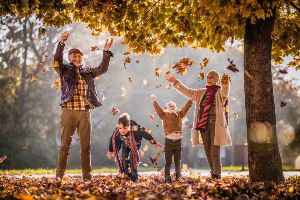 seniors playing in fall leaves with grandchildren