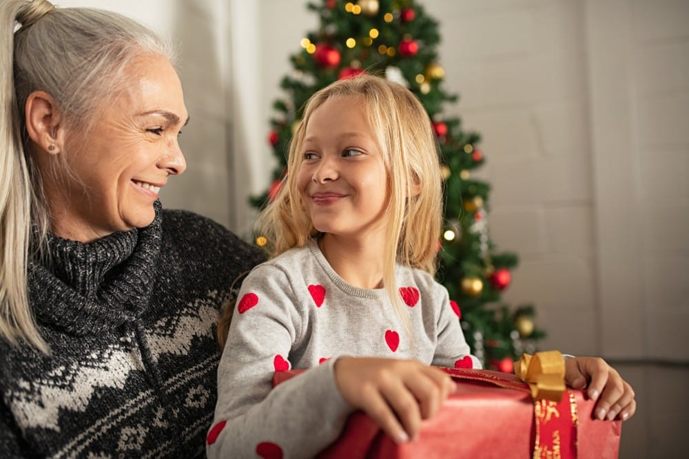 grandparent giving grandchild Christmas gift with tree in background