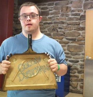 """Kristie's son holds a dustpan with """"Golden Dustpan"""" written on it."""