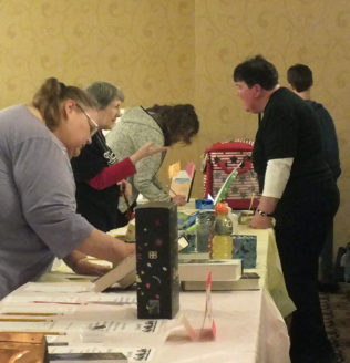 Women viewing auction table at the Evening of Entertainment event.