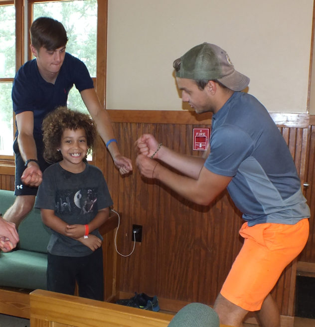 Young boy playing with camp counselors.
