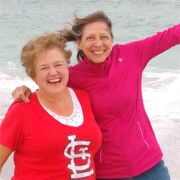 Peggy and Carol have their arms around each other on a beach.