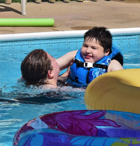 Young boy learning to swim.