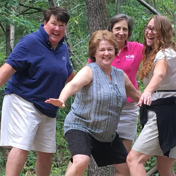 Recreation Council staff stand in the woods, posing for the camera.