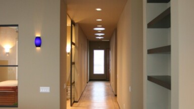 Living room build features custom shelving in contrasting dark wood