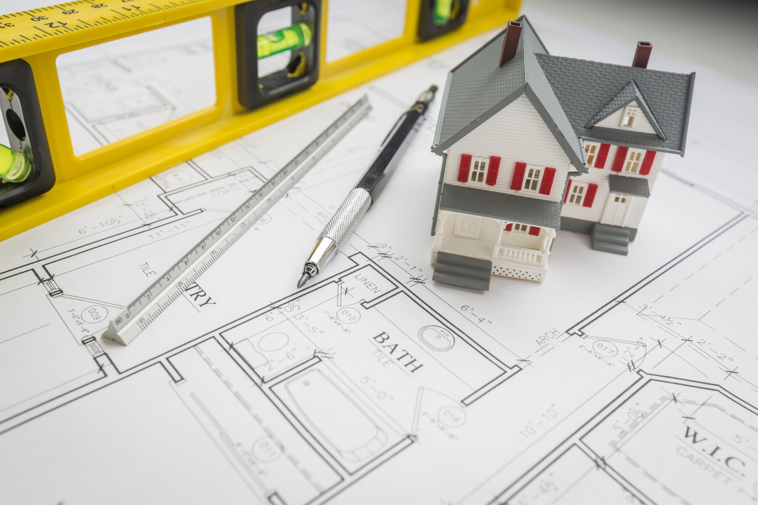 Model Home, Construction Level, Engineer Pencil and Ruler Resting on Custom House Plans.
