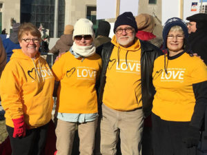 Picture of four Peoples Church members in yellow Standing on the Side of Love shirts