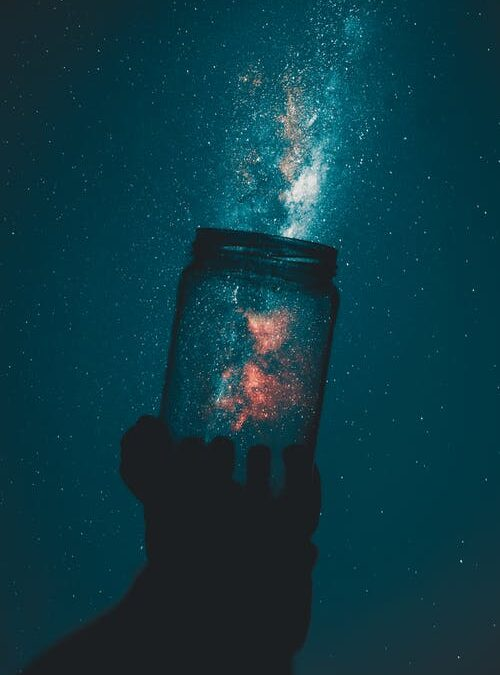 Photo of a glass jar held up so it appears to hold stars.
