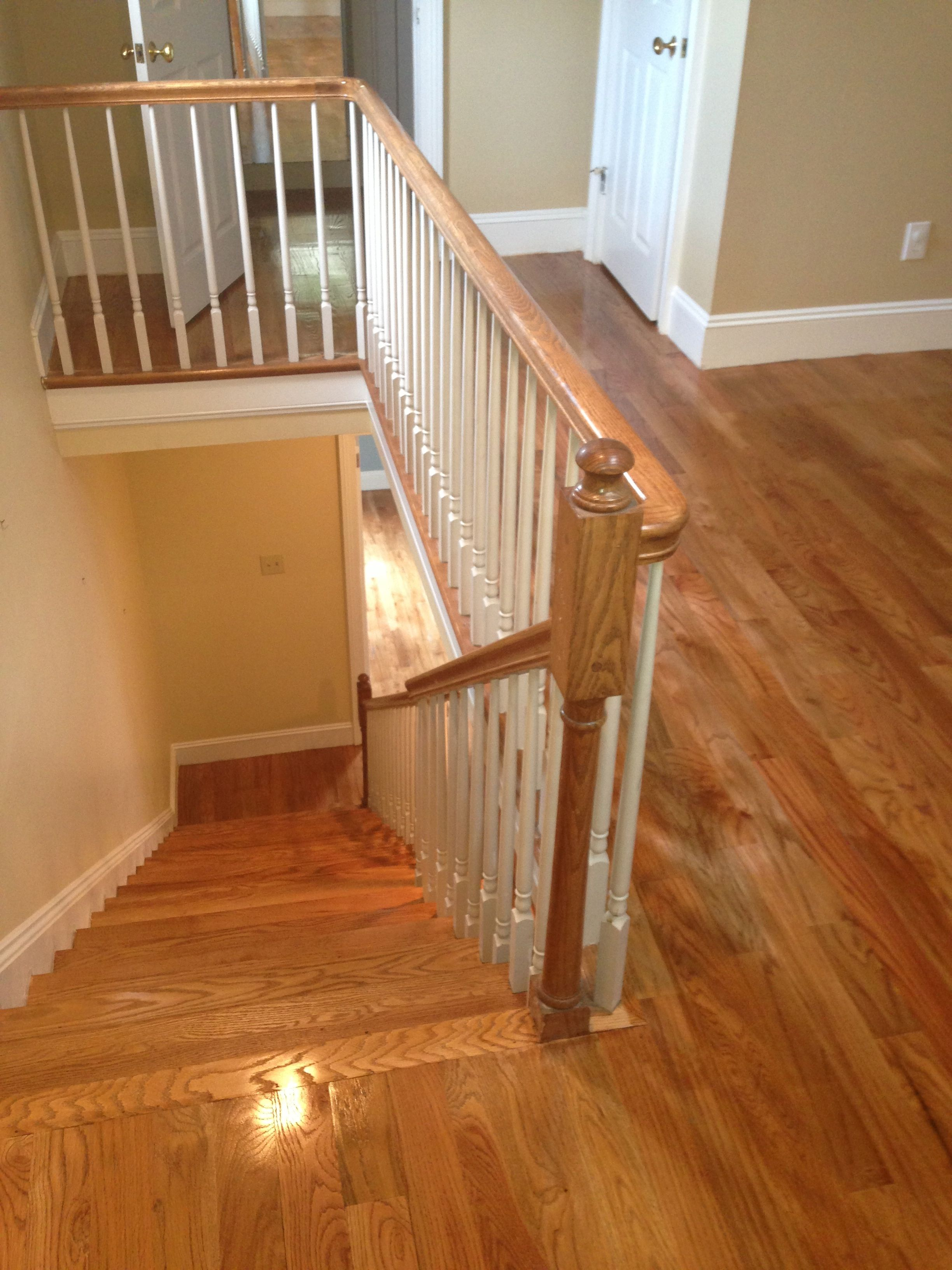 A photo of a staircase and upstairs balcony of newly polyurethaned red oak hardwood flooring.
