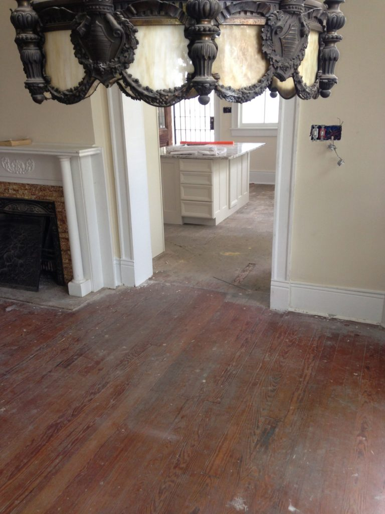 Hardwood floors in a living area and kitchen prior to being refinished.