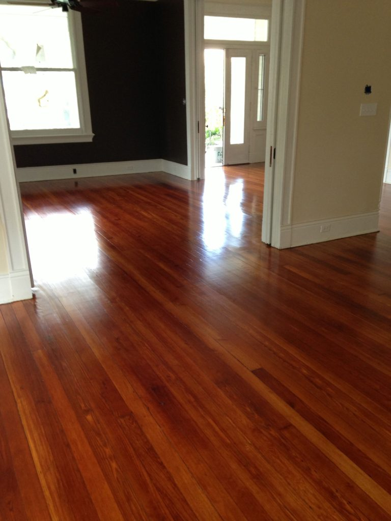 Shiny refinished hardwood flooring in front room and living area.