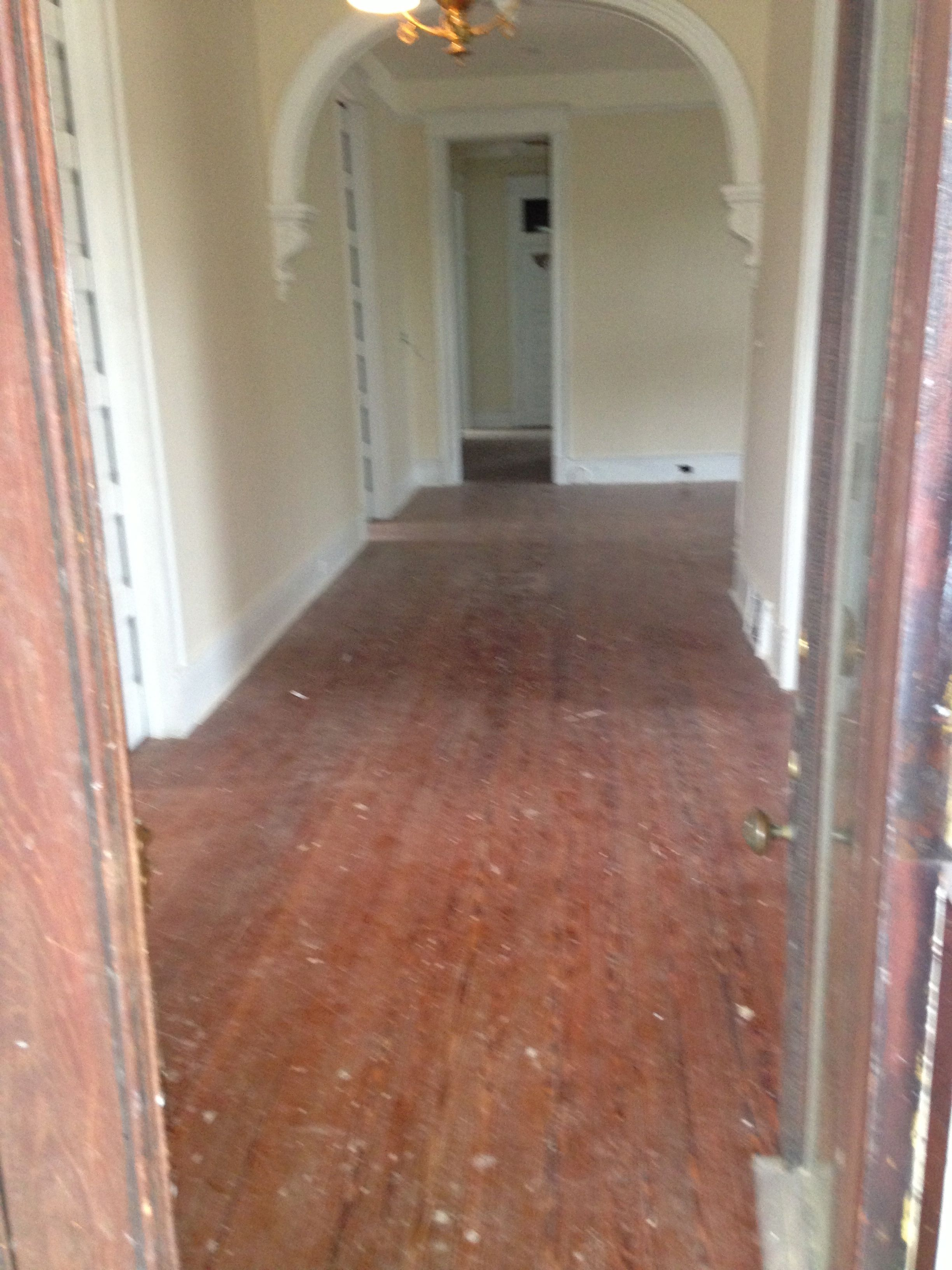 Pictured dusty and scuffed hardwood floors prior to refinishing
