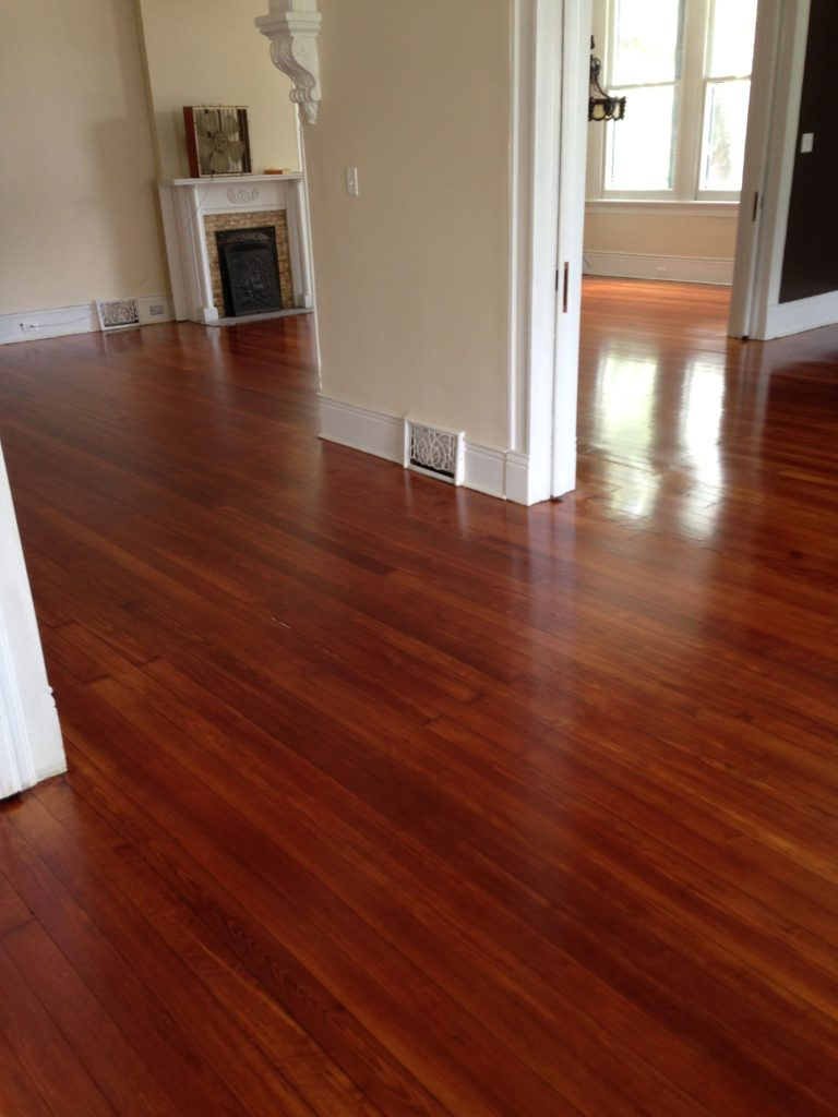 Shiny polyurethaned hardwood floors in living room with a fireplace