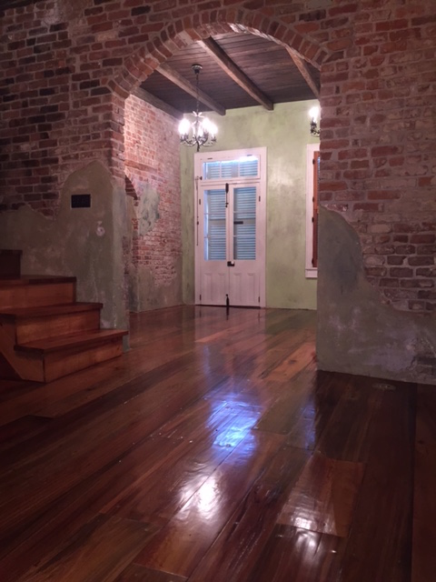This is a photo of a historic cottage with wide planked pine hardwood floors with shades of red and dark brown.