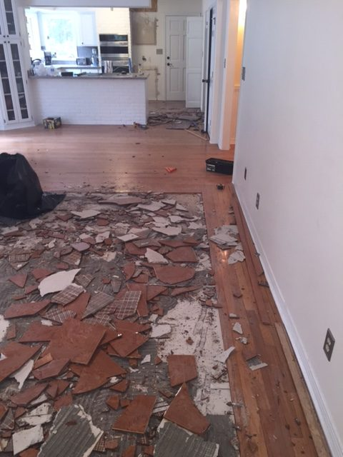 Picture shows broken tile in the process of being removed. It is a square section of a living room surrounded by hardwood flooring.