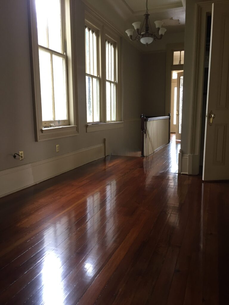 This is a hallway with a stairwell of refinished glossy pine floors.