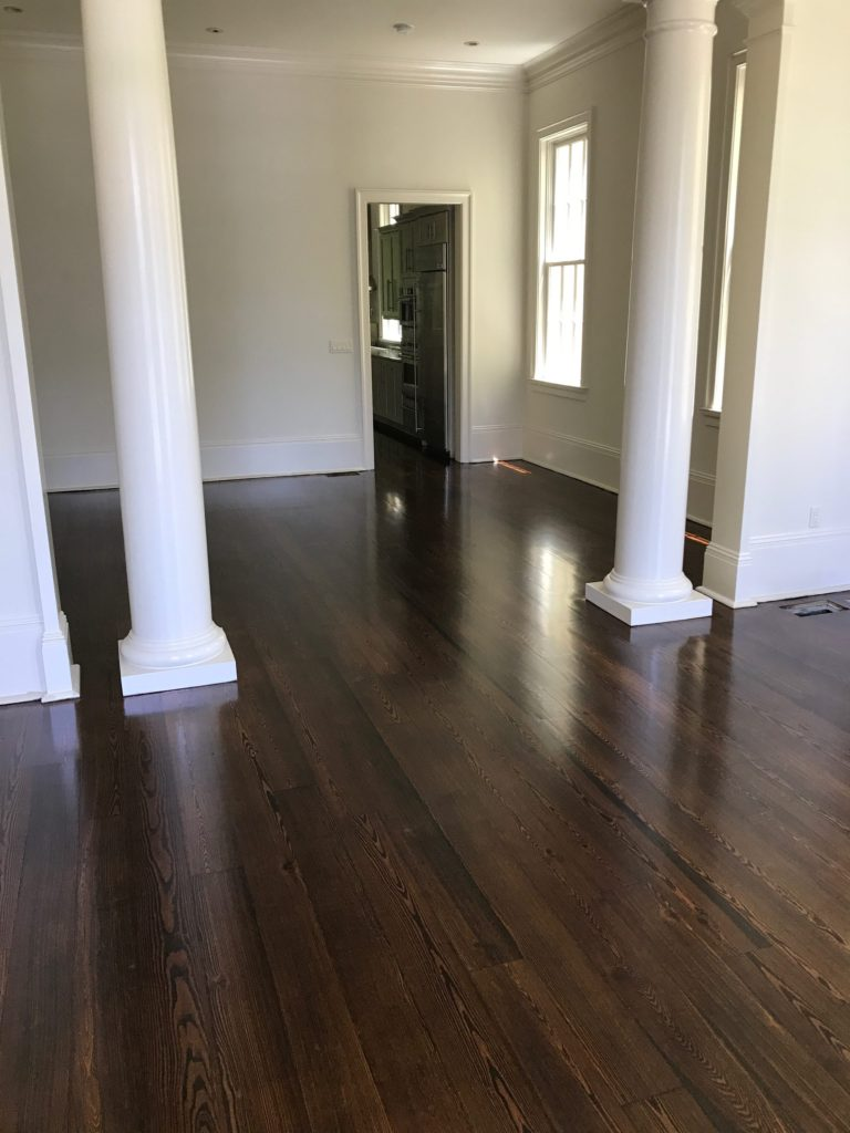 Pictured is a living area of dark stained red pine flooring between two columns.