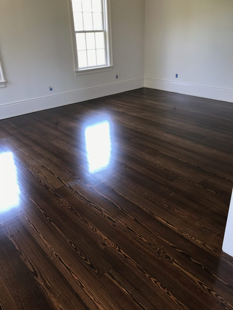 Pictured is a room with dark stained red pine hardwood flooring. The floors are glossy with the contrasting grain visible.