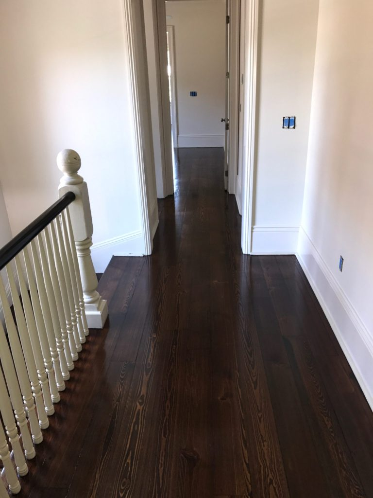 Pictured is a dark stained red pine hallway at the top of a staircase.