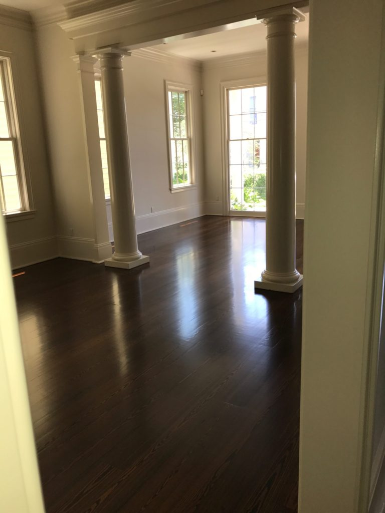Pictured is a living room with dark stained red pine hardwood flooring.