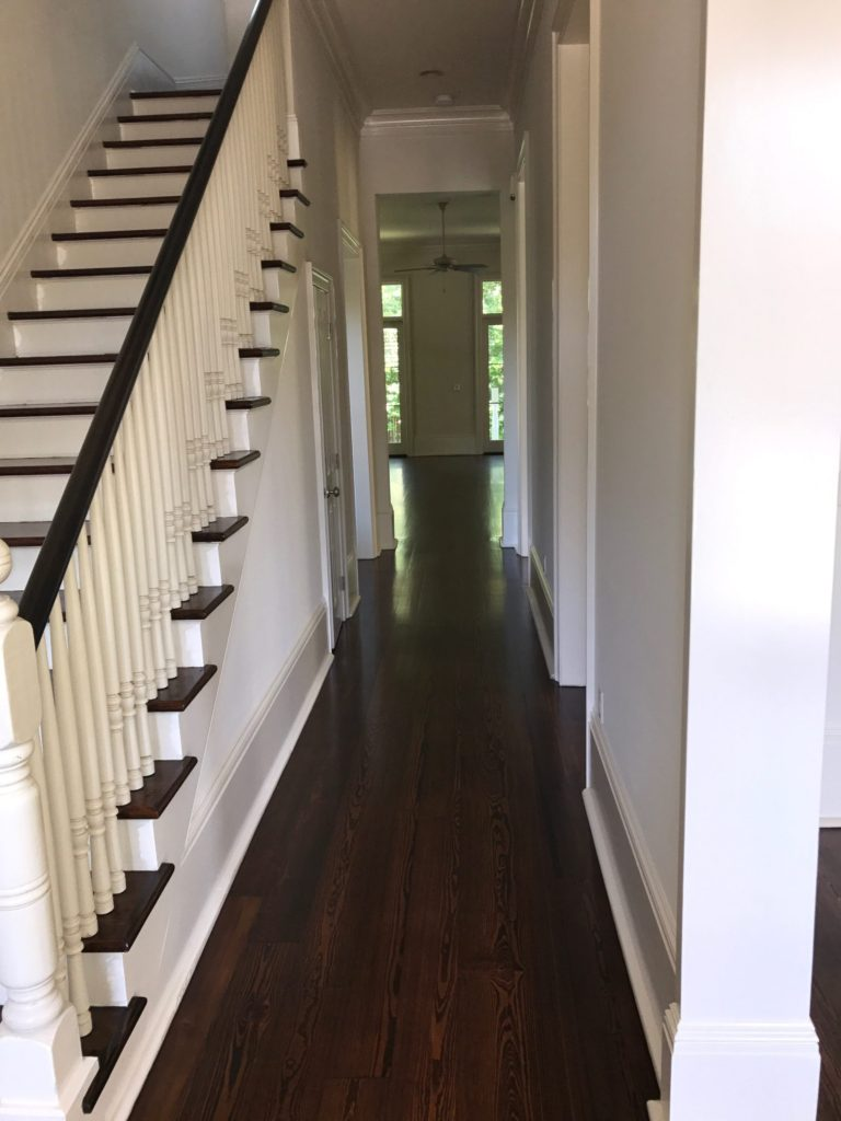 Pictured is a hallway with red pine floors with a dark stain.