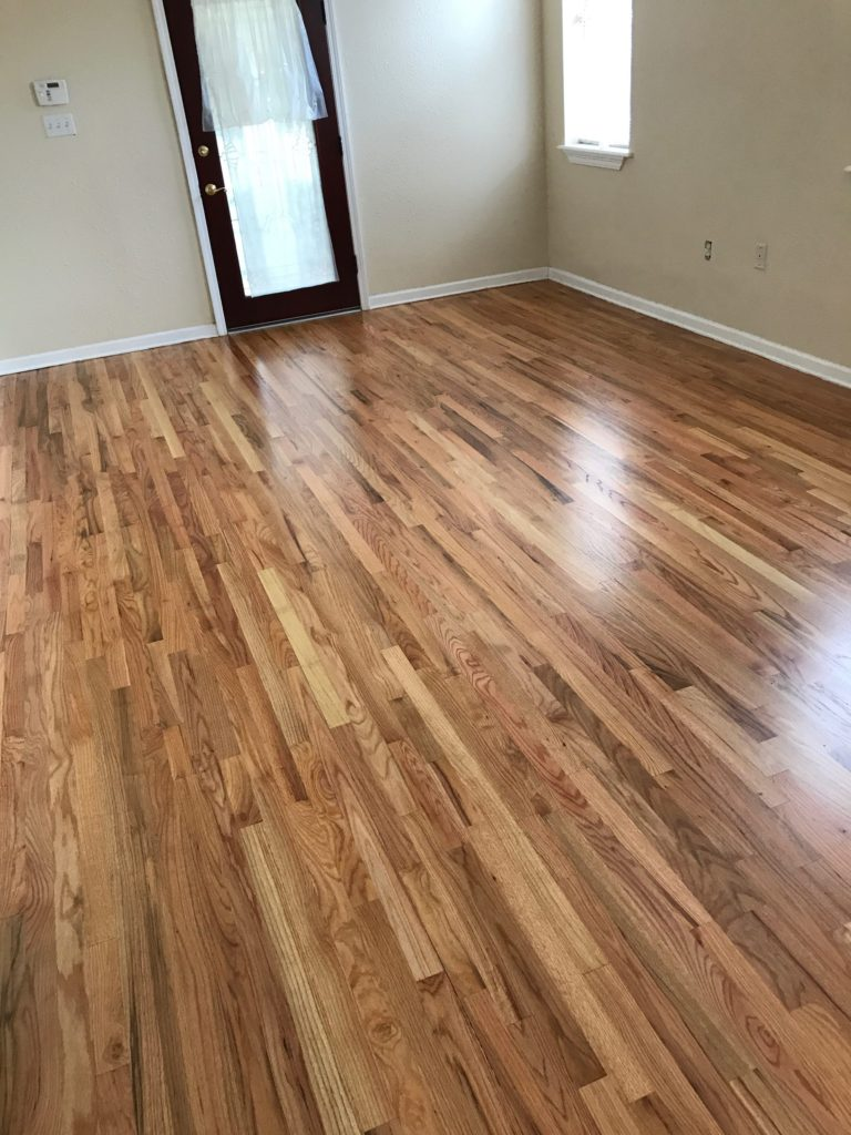 Pictured are red oak floors with a natural finish. The contrasting colors in the wood grain are eye catching with shades of red tones, browns, and creamy white.