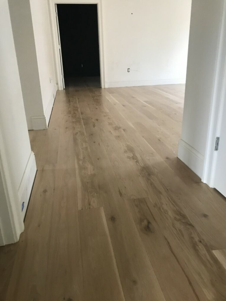 This is a photo of a hall with white oak flooring with a satin finish. It has a weather washed appearance.