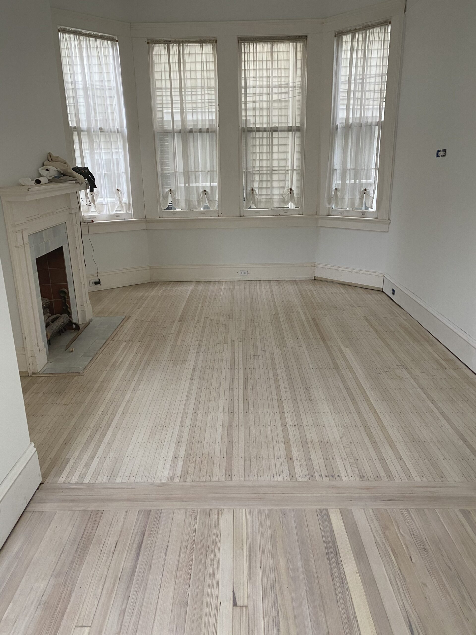 Bleached and white wash finished red oak and red heart of pine in a living room with a bay window and white fireplace. Oak wood is nailed down and visible, called Philidelphia strips.
