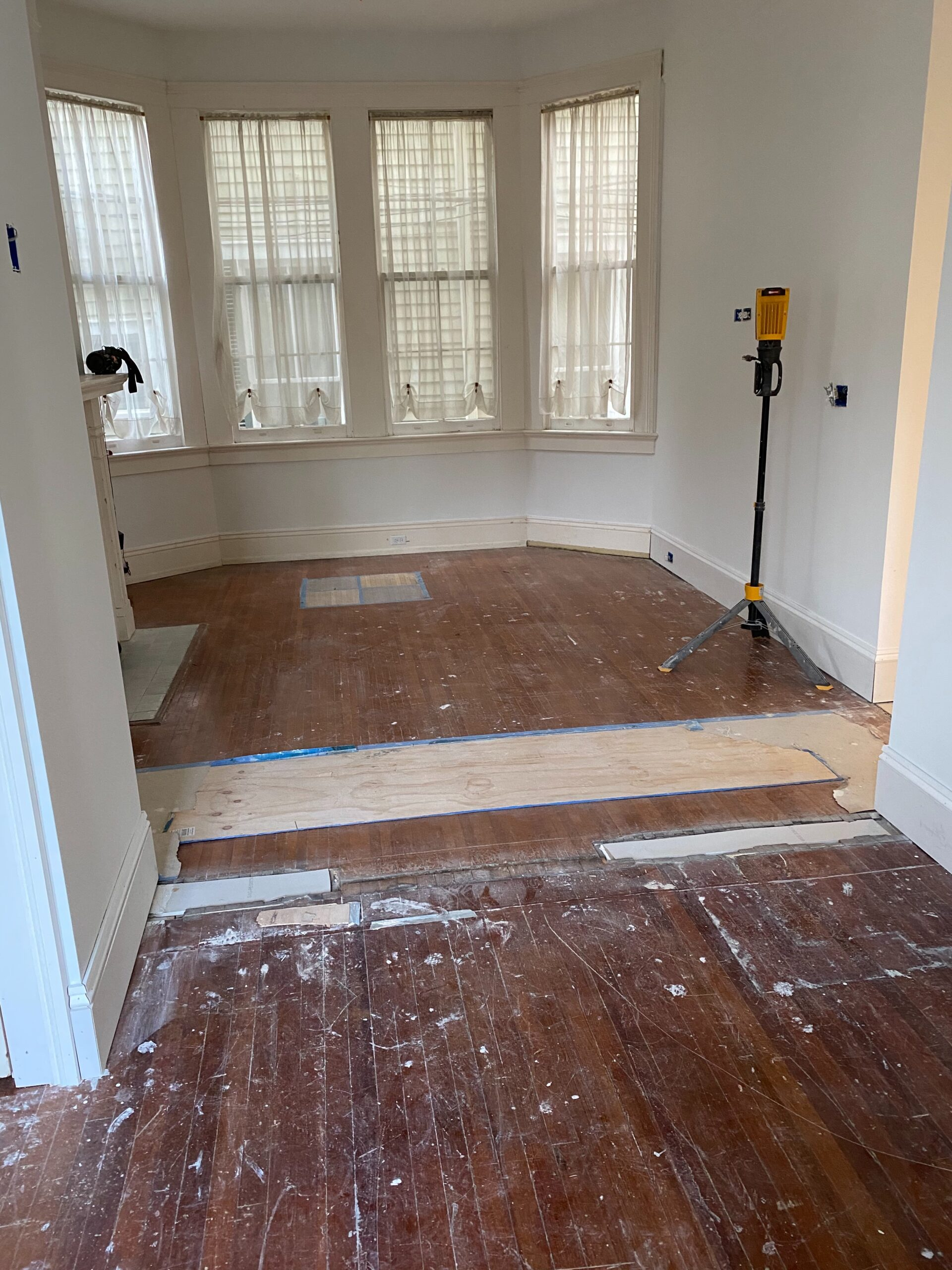 Before photo of red oak and red heart of pine in a living room with a bay window and fireplace