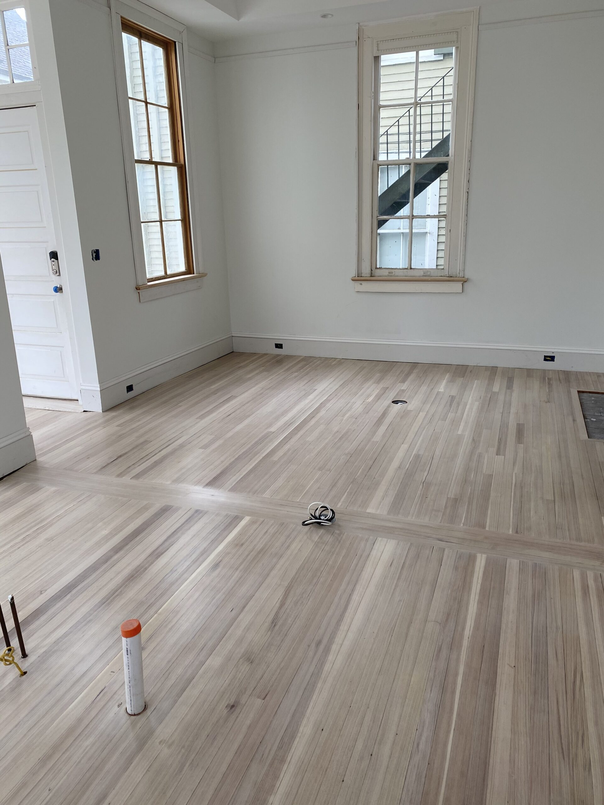 Beautiful white wash finish red heart of pine hardwood flooring in a den area with white walls