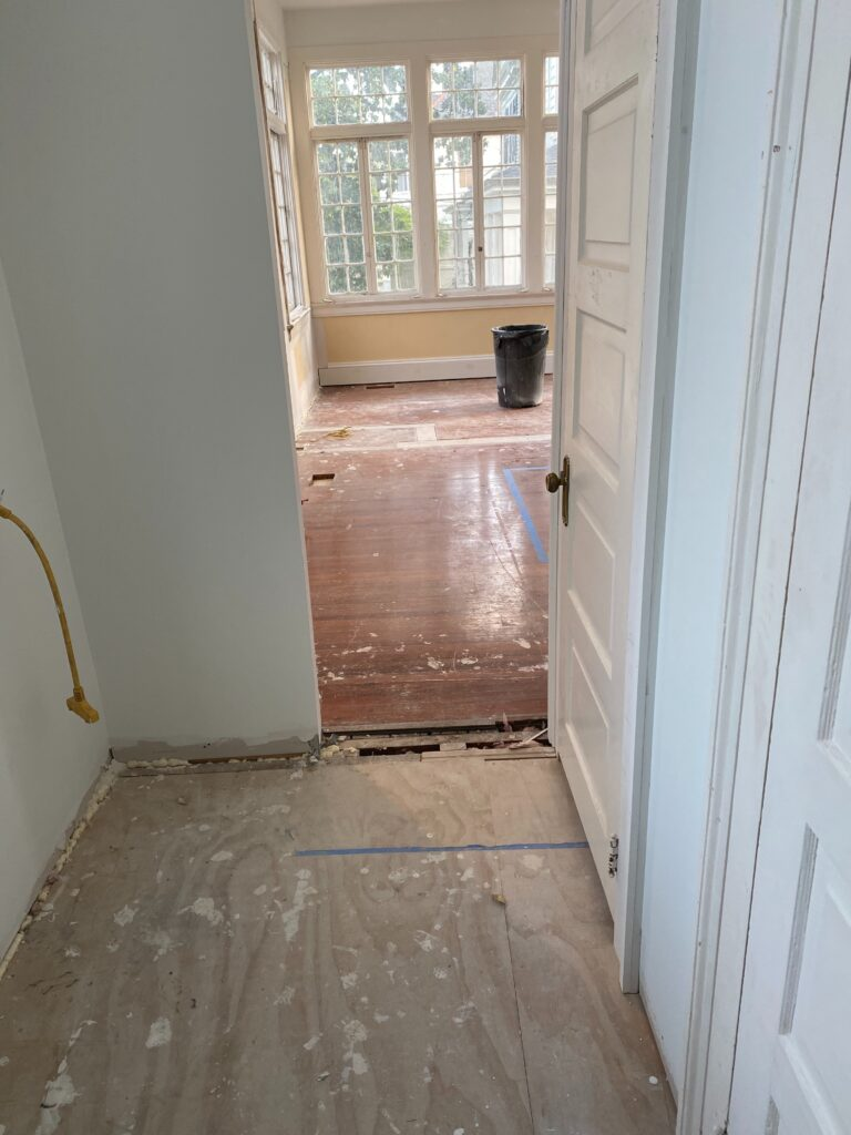 Before photo of stripped hallway and room with red heart of pine prior to bleaching with a white wash finish
