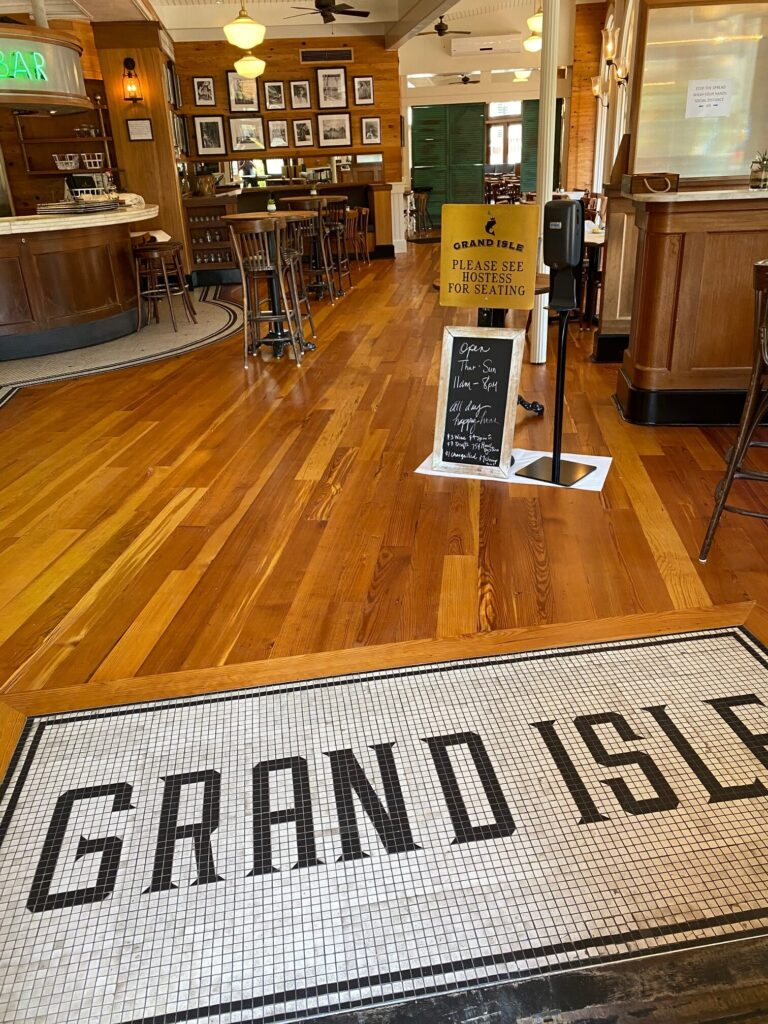 Photo of refinished antique heart of pine floors in a restaurant. Entrance with tiny small tiles reading Grand Isle surrounded by newly finished wooden floors.