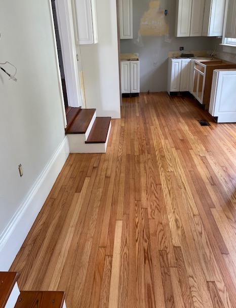 Refinished red heart of pine stairs dropping into refinished red oak flooring in a split level kitchen
