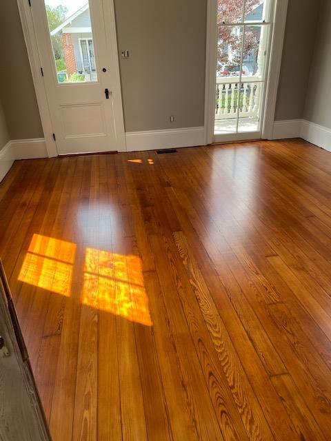 Refinished Red Heart of Pine Hardwood Flooring with an entry door and window
