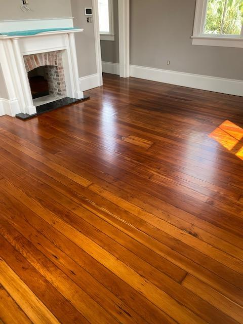 Refinished Red Heart of Pine Hardwood Flooring with a fireplace in the room
