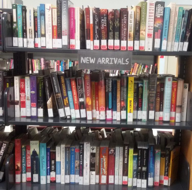 "Full book shelves labeled with ""New Arrivals"""