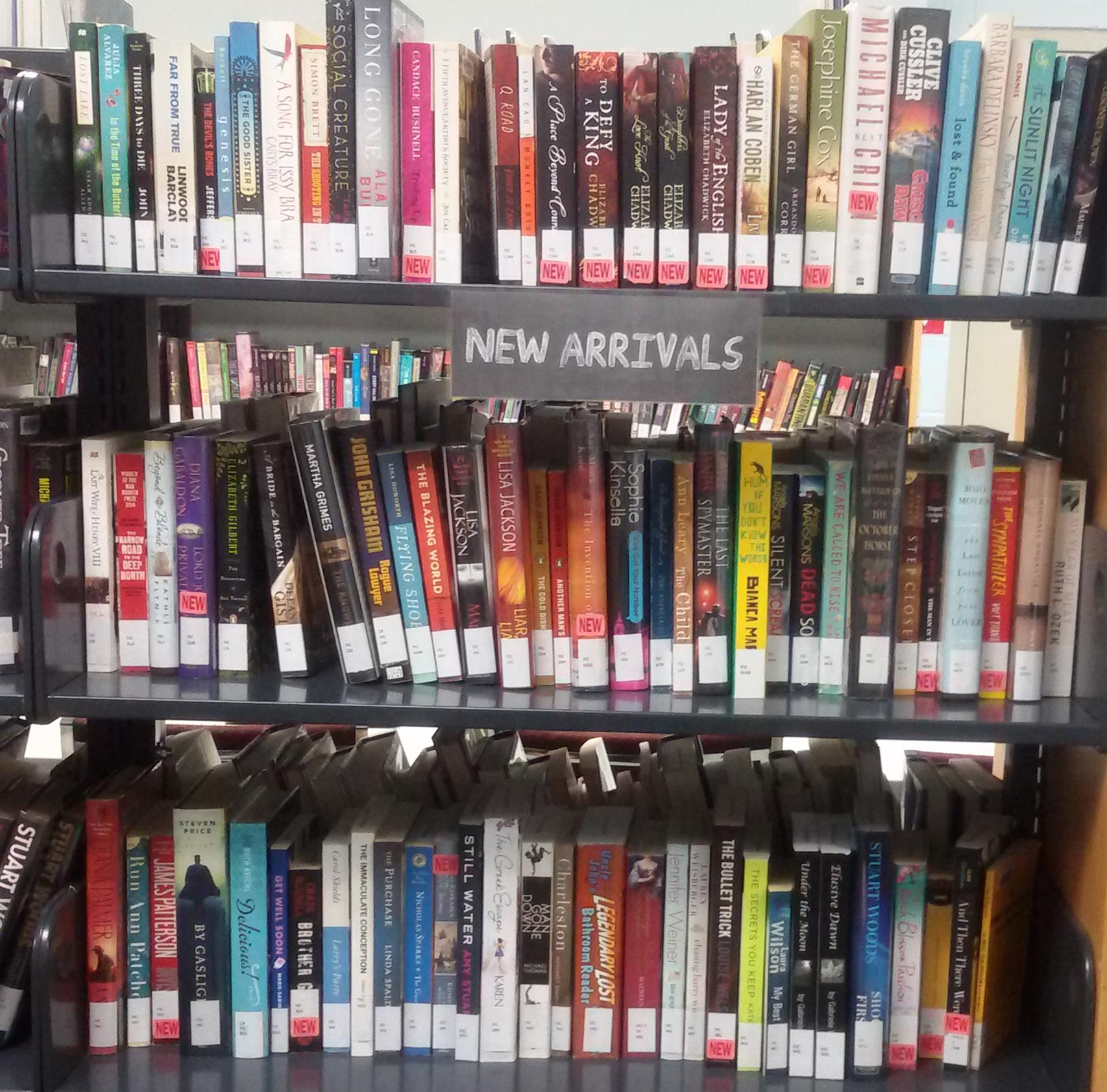 """Full book shelves labeled with """"New Arrivals"""""""