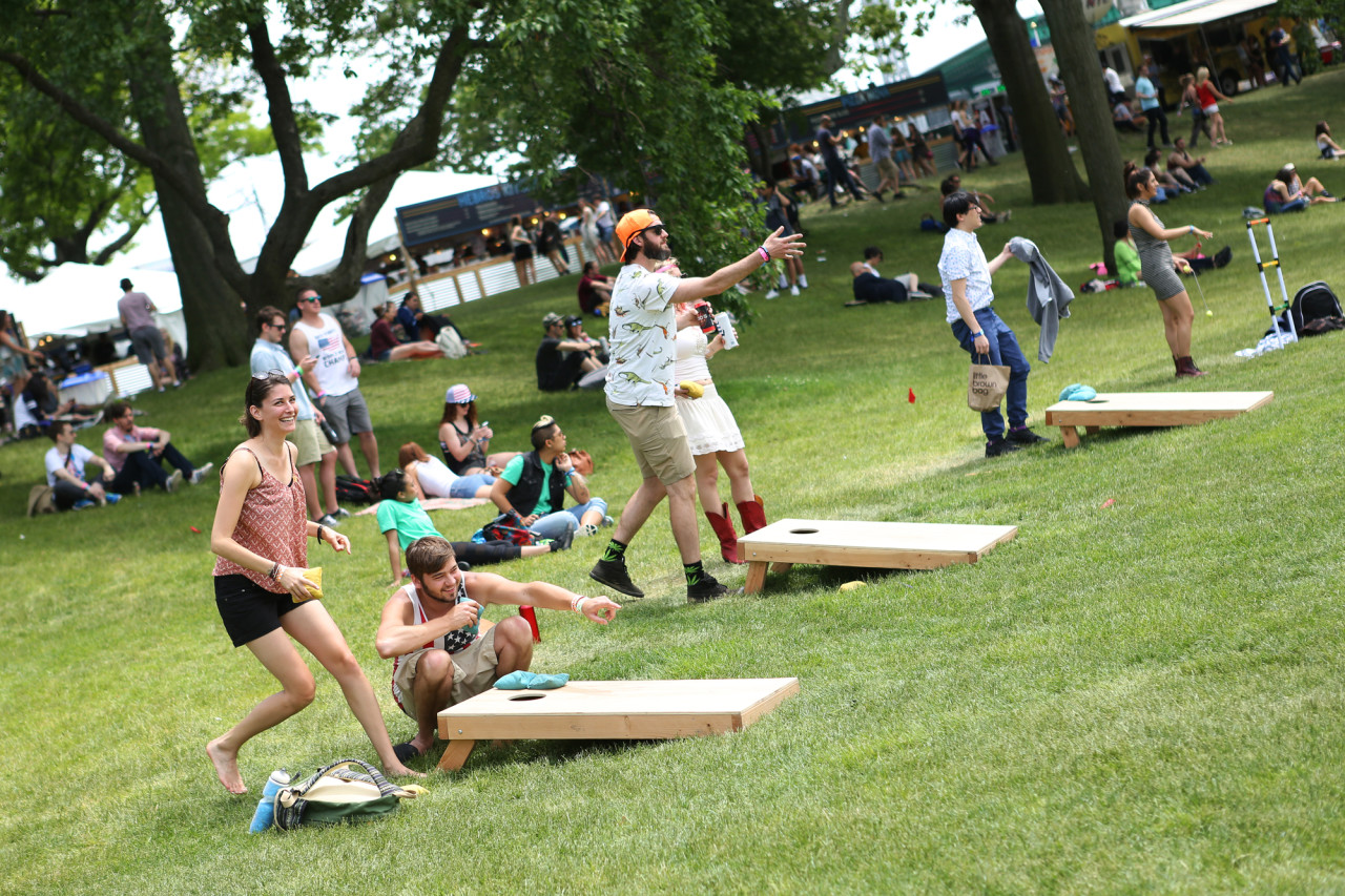 Festival goers playing cornhole early on Saturday afternoon at Governors Ball on Randall's Island, New York, on June 6, 2015. (© Michael Katzif – Do not use or republish without prior consent.)