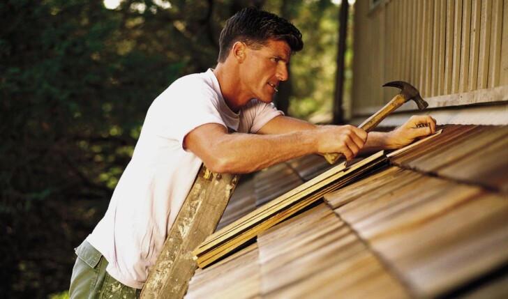 man patching roof