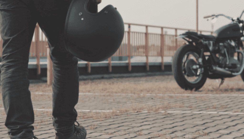 man with helmet in hand walking towards a motorcycle