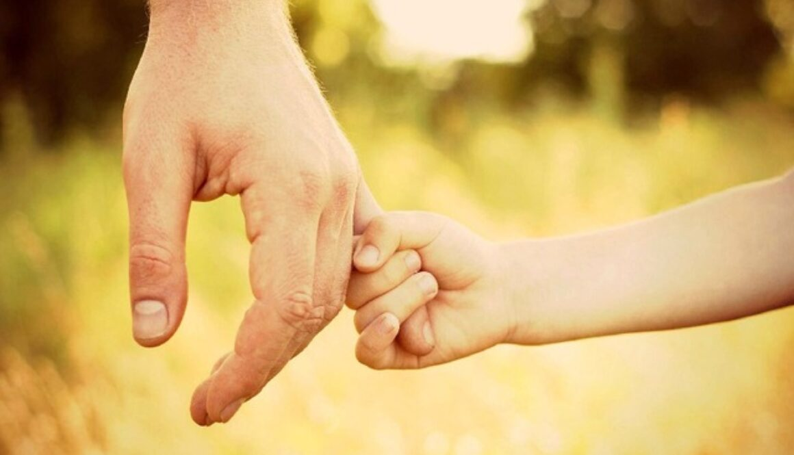 child holding onto the pinky finer of an adult