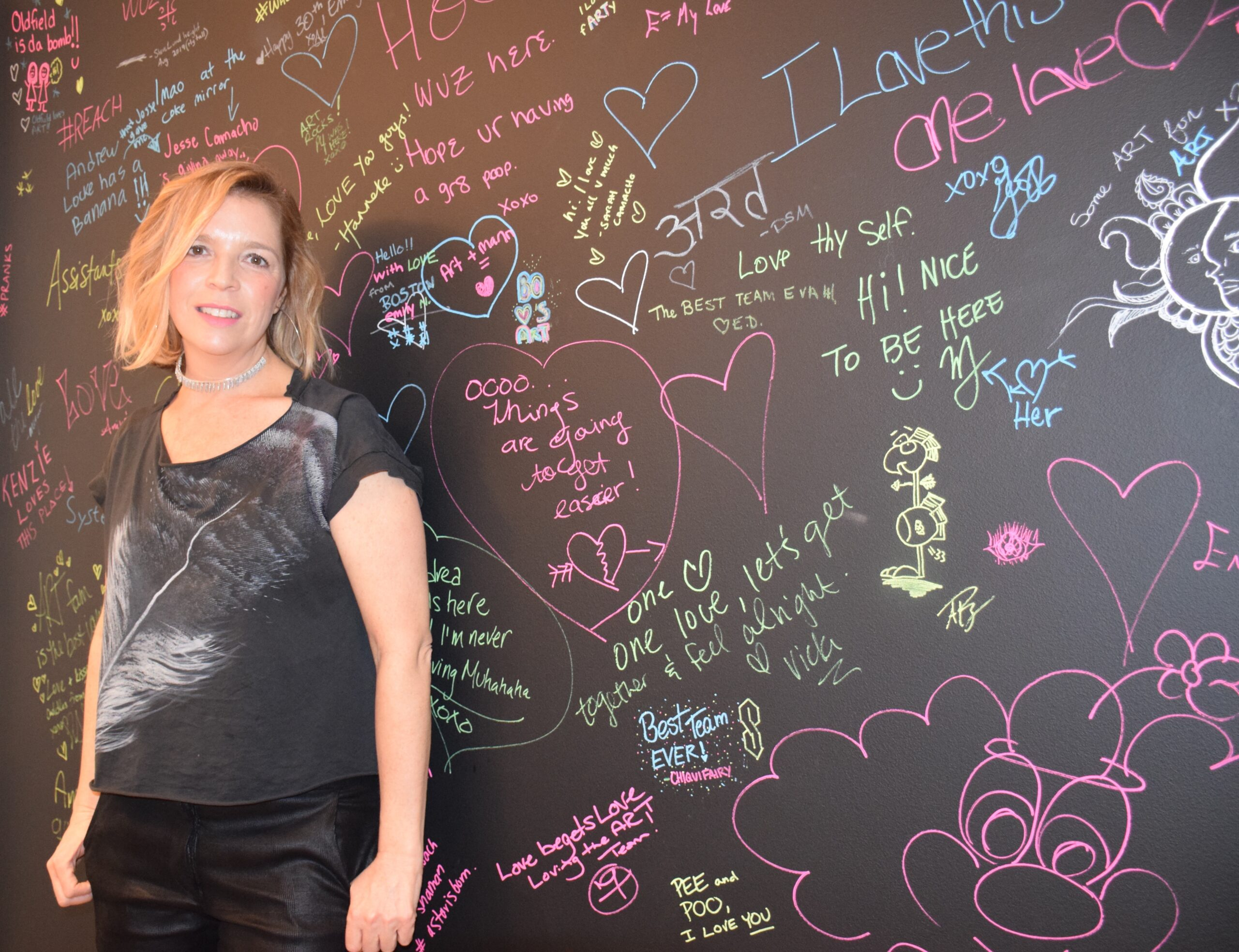 Amanda by the ART Agency Wall where clients can leave love notes